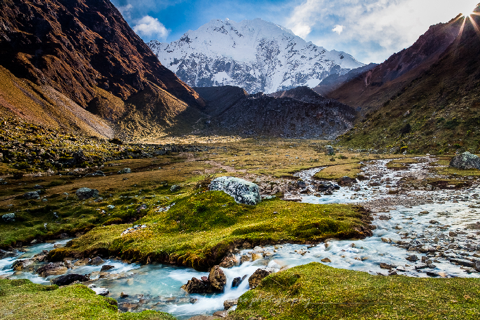The sun flares over a ridge while we stop to take in the beautiful alpine creek on our way to Salkantay Pass (15,000 ft) en route to Machu Picchu, Peru.